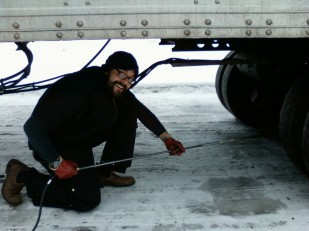 Image of trucker thawing his frozen brakes with a weed flaming device.