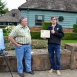 Chair Rodger Brandt and tree committee member Craig Leech present the award for the T.J. Howell Brewer Spruce.